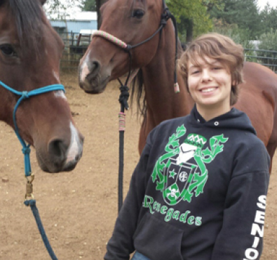 Graduate Phoebe Jud standing with two horses.