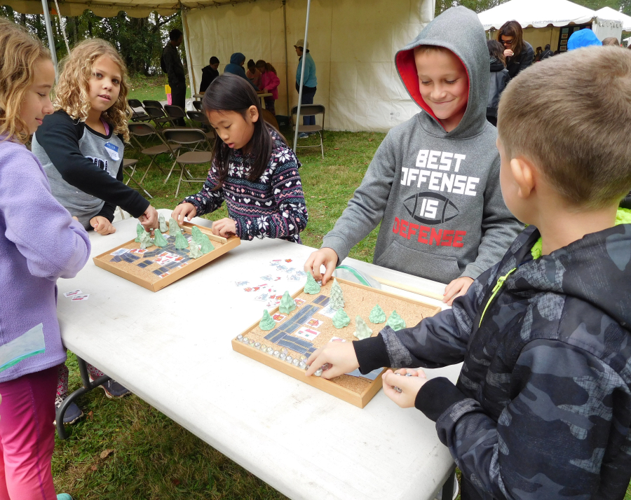 Fourth-graders from Woodburn Elementary work with a scale model of an urban watershed.