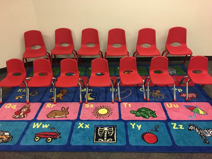 Small red chairs on a colorful rug.