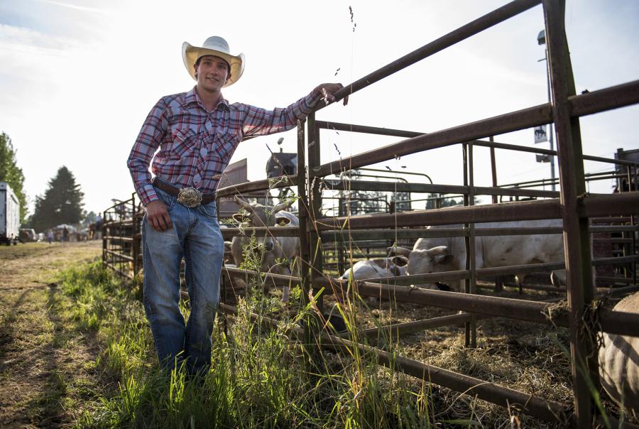 Cody Hudson leans against fence railing.