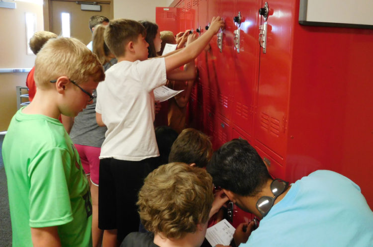 Middle school students learning how to open lockers.